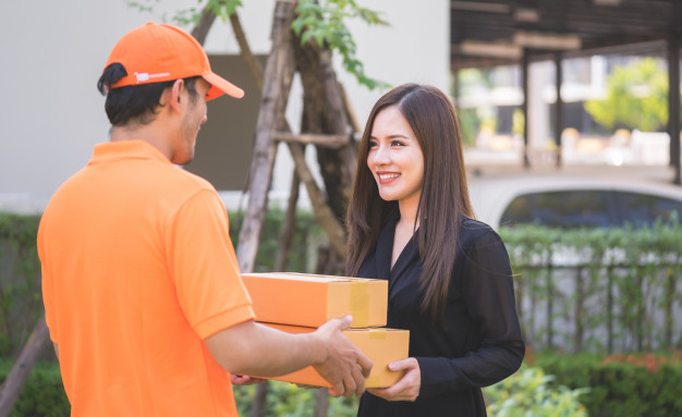 delivery-man-orange-bringing-woman-package_39408-749